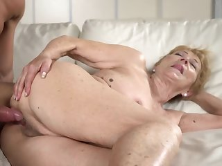A nasty old granny gets a hard locate between her legs on the sofa